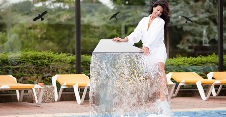 Dame steht an kleinem Wasserfall des Pools im Saunapark Kamperbrück